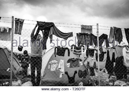 Refugee man drying laundry on barbed wire at Greek-Macedonian border.  Idomeni, Greece, 7 March 2016. The refugee camp to which thousands of immigrants, mainly Syrians, are coming. It is occupied by people from different social strata. They are all found there fleeing the war, death and starvation. They continue their journey through Macedonia to the north and west of Europe. Not everyone manages to pass the verification of the documents, which leads to the separation of families. The refugees are living in difficult conditions and sleeping in overcrowded and soaked tents. - Stock Photo