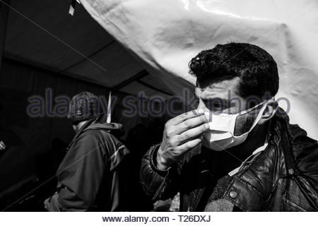 Because of the unhygienic conditions that prevail in the camp, some people wear masks at Greek-Macedonian border.  Idomeni, Greece, 5 March 2016.The refugee camp to which thousands of immigrants, mainly Syrians, are coming. It is occupied by people from different social strata. They are all found there fleeing the war, death and starvation. They continue their journey through Macedonia to the north and west of Europe. Not everyone manages to pass the verification of the documents, which leads to the separation of families. The refugees are living in difficult conditions. - Stock Photo