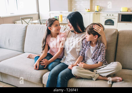 Mother is sitting on sofa with her kids. She is hugging them. Woman looks at daughter. She holds hand on boy's head. Happy kids are looking at mom - Stock Photo