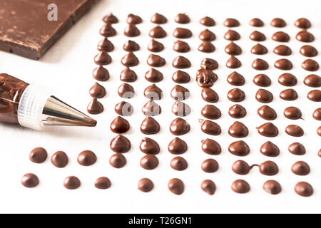 Food concept making homemade chocolate chips for bakery on white background - Stock Photo