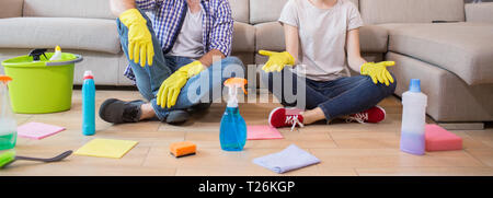 Cut view of man and woman sitting on the floor and resting. She is meditating. Man and woman has their legs crossed. There are cleaning equipment all  - Stock Photo