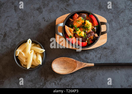 Vegetarian letcho with baked aubergine, zucchini, pepper in tomato sauce. Dish served with pasta. - Stock Photo