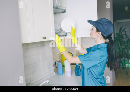 A picture of cleaner putting plate in cupboard. It is opened. Girl wears blue uniform and yellow gloves. She cleans space - Stock Photo