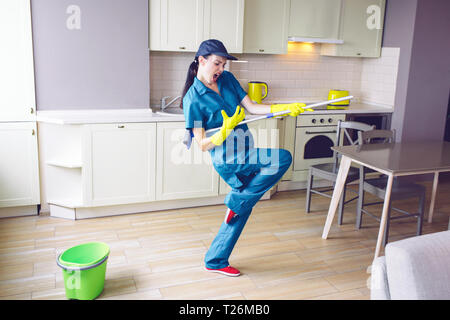 Funny worker dancing in kitchen. She pretends playing on guitar. But girl has mop in hands in stand of that. She is rocking and relaxing - Stock Photo