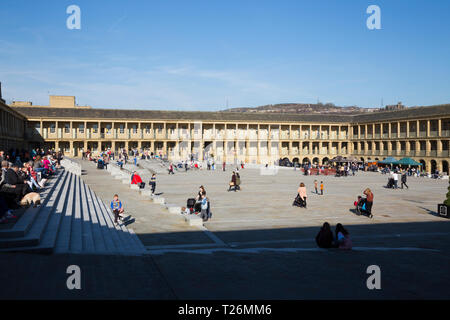 People / visitors / tourists sit & relax on the steps inside the quadrangle of  restored The Piece Hall. Sunny / sun & blue sky. Halifax, West Yorkshire, UK - Stock Photo