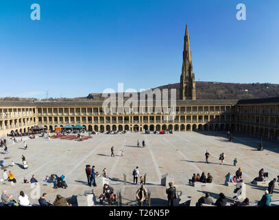 Panoramic / panorama. Visitors relax in The Piece Hall with Square Chapel church spire behind in the background. Sunny / sun & blue sky. Halifax, West Yorkshire, UK. (106) - Stock Photo