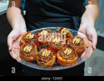 woman offering quince dessert on serving plate. kitchen apron - Stock Photo