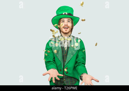 Happy rich young man in saint Patrick's suit spreading golden coins up and smiling. They fly. Guy look up. Isolated on grey background - Stock Photo