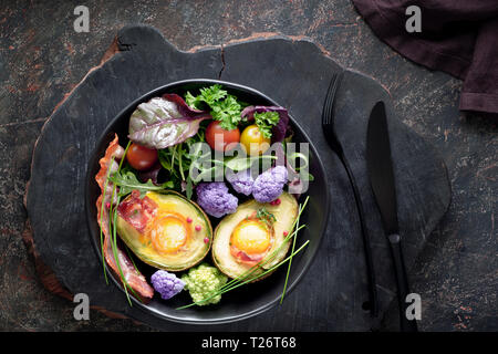 Baked avocado with egg and bacon ,flat lay on dark background - Stock Photo