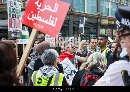 London, UK. 30th March, 2019. Pro-Palestinian campaigners attending a Rally for Palestine outside the Israeli embassy to demand freedom, justice and equality for the Palestinian people stand in front of a small pro-Israel counter-protest Credit: Mark Kerrison/Alamy Live News - Stock Photo