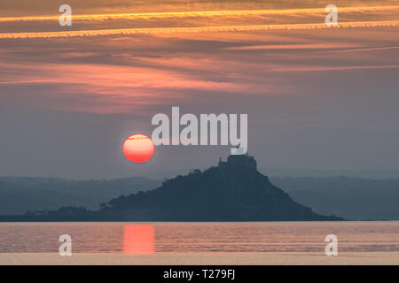 Red sun rising beside St Michaels Mount Cornwall reflecting in the sea - Stock Photo
