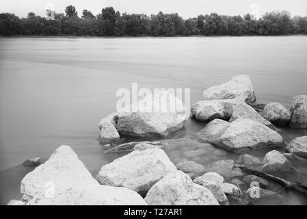 Long Exposure Danube Landscape with Tree Line and White Rocks - Stock Photo