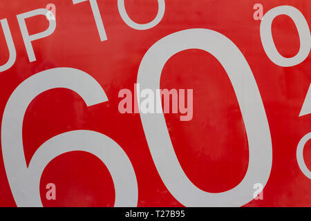 Red sign Sale up to 60 percentage off in shop window display - Stock Photo
