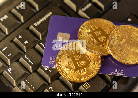 An bitcoin coin with blue credit card on top of computer keyboard at background, cryptocurrency accepting for payment and finance concept - Stock Photo