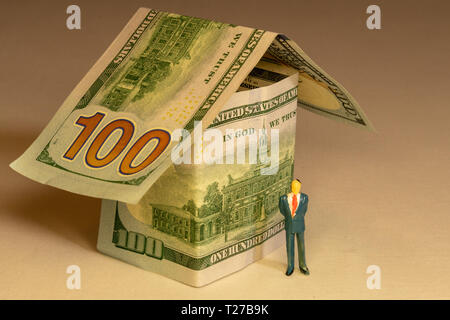 Business man at front of the house made from hundred dollar bills. Real estate expenses building mortgage and property concept. - Stock Photo