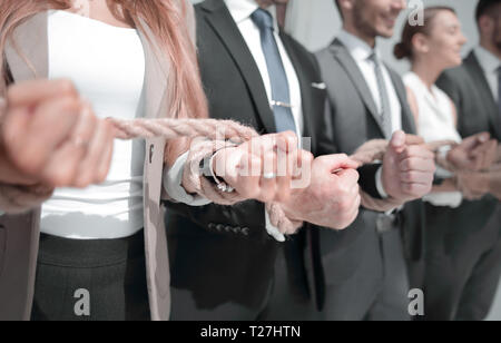 Hands of business people connected by ropes - Stock Photo