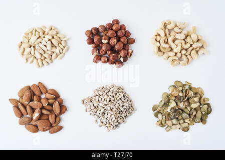 peanuts, cashews, hazelnuts, almonds, pumpkin seeds and sunflower seeds on white isolated background - Stock Photo