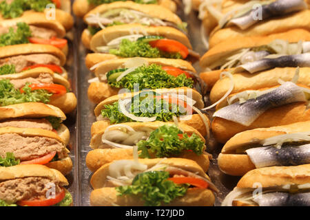 Fresh sandwiches with fish, tomato, lettuce salad, pate, cucumber and onion - Stock Photo