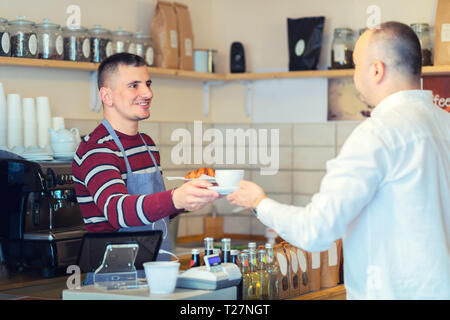 Barista serving cup of coffee to customer at counter in small coffee shop – cheerful mature waiter giving hot cappuccino and butter croissant to man - Stock Photo
