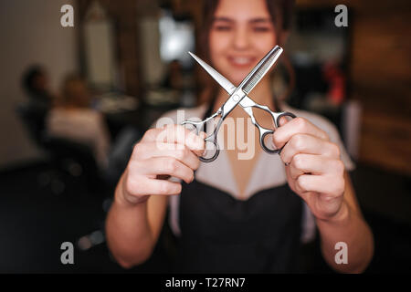 Close-up of professional metal hairdressing cutting scissors in hairdressers hands. Hairdressing tool - Stock Photo