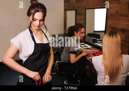 Beautiful woman hairdresser with black apron taking hair professional clip before hairstyling on salon background. Beauty and people concept - Stock Photo