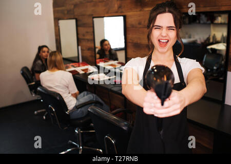 Ready to work Emotion beautiful woman hairdresser with black apron looking at camera while holding professional hair dryer on salon background. Beauty - Stock Photo