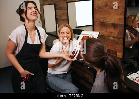 Professional hairdresser and blonde young woman laughing while choosing hair color from palette in beauty salon - Stock Photo