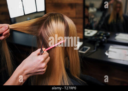 Hairstylist hands holding strand of blonde hair while combing it before haircut in salon - Stock Photo