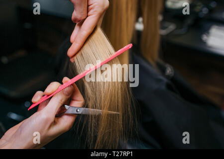 Close-up of hairstylist hands combing blonde hair before haircut in salon - Stock Photo