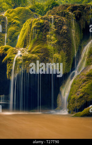Beautiful detail of a waterfall flowing onto a moss covered rock with a cave beneath shot in Romania with a long exposure - Stock Photo