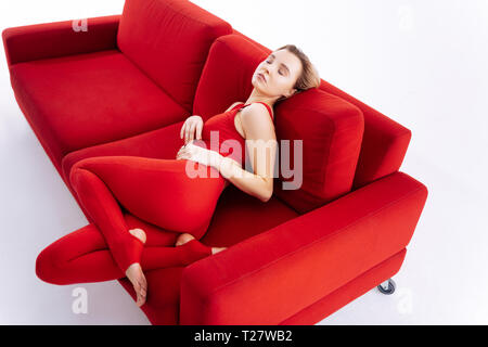 Attractive fit blonde woman having rest on the sofa - Stock Photo