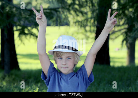 Portrait of boy showing victory hand sign on nature background - Stock Photo