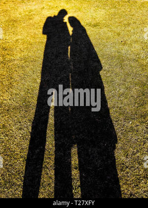 shadow of a man and a woman in love holding handsin a garden. - Stock Photo