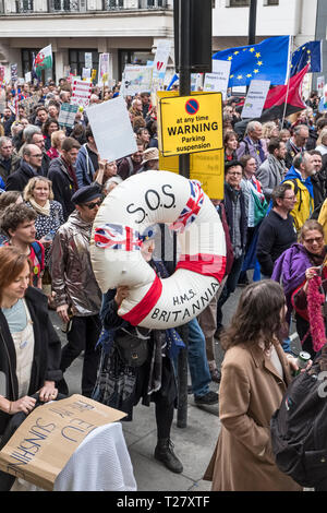 London, UK, 23rd March 2019. A million protestors march against Brexit and in support of a second referendum. A protestor wearing a giant lifebelt - Stock Photo