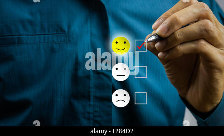 Conceptual the customer responded to the survey. The client using hand choose happy face smile icon on screen. Depicts that customer is very satisfied - Stock Photo