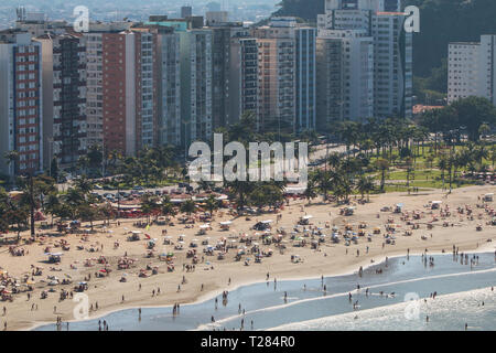 High-angle view of hundreds of people enjoying the beach on a Sunday at Sao Vicente, on July 8, 2018 in Sao Vicente, Brazil. - Stock Photo