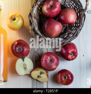 Apple juice in a glass bottle with a natural sludge. Fresh red apples. - Stock Photo