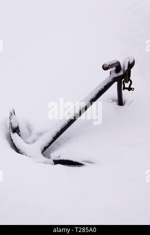 HOFN/ ICELAND:  FEBRUARY 9, 2016:  A ship's anchor lies half-buried in snow in the fishing village of Höfn, along Iceland's southern coast. - Stock Photo