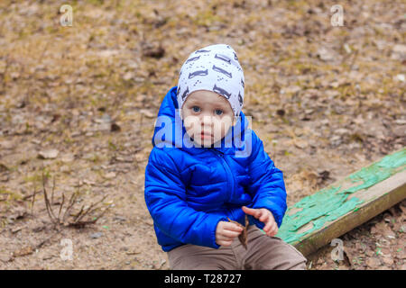 A little boy is sitting in the sandbox. Children's games. Sand Games - Stock Photo