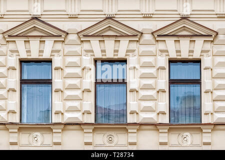Three rectangular Windows with triangular cornices on a beige background of the wall with a bas-relief . From a series of windows of St. Petersburg. - Stock Photo