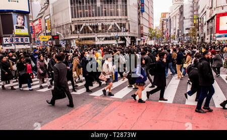 Crowd of people, walking in various directions, crossing the Shibuya crossing, Tokyo, Japan - Stock Photo