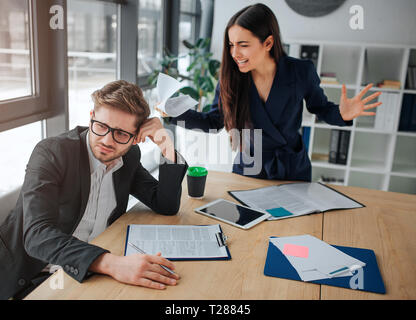 Young woman screaming on man. They are in white meeting room. She stand upon him waving hands and yelling. Guy looks tired and upset - Stock Photo