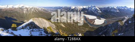 Wide Panoramic Landscape of Snowcapped Mountain Peaks and Bow River Valley in Alberta Foothills of Canadian Rockies near Banff National Park - Stock Photo