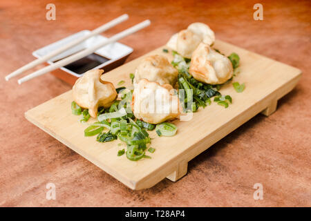 Gyoza with soy sauce on a wooden table - Stock Photo