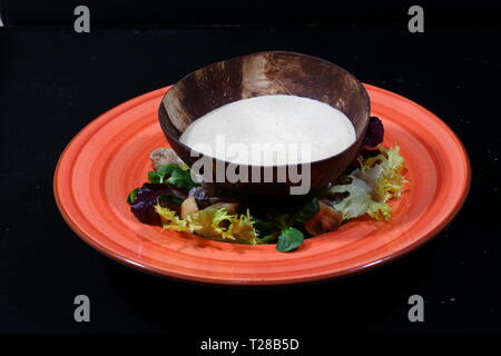 Mushroom soup puree on a black background in a wooden plate - Stock Photo