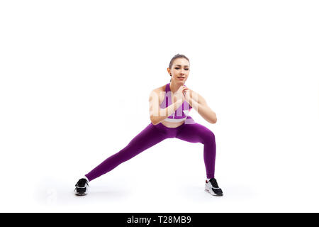 A young woman coach in a sporty pink   short top and gym leggings makes lunges  by the feet side, hands are held out to the side   on a  white isolate - Stock Photo