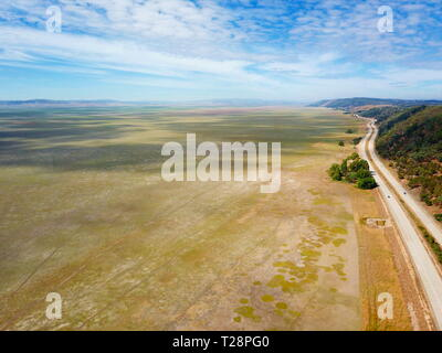 Empty Lake George nestled between farmland and Federal Highway in Australia. Lake George is an endorheic lake, as it has no outflow of water to rivers - Stock Photo