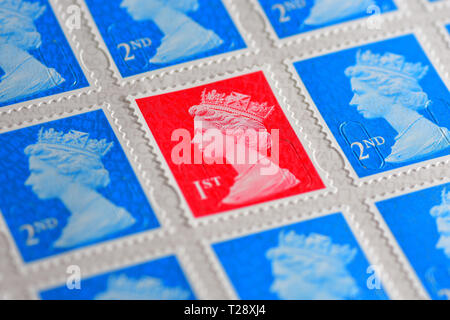 One red British 1st Class Stamp with blue 2nd class stamps - Stock Photo