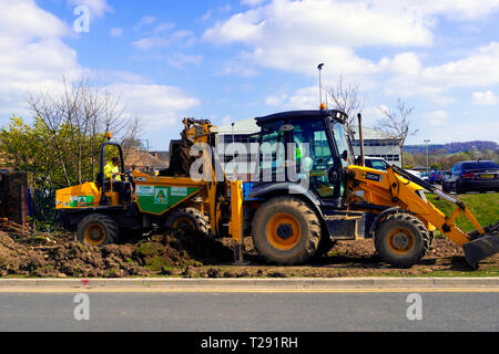 Workmen using a JCB 3CX excavator loading excavated topsoil into a dumper truck for removal - Stock Photo