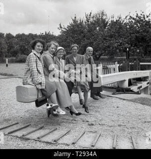 1950s, historical, a small group of ladies and one gentleman - smoking a pipe-  sitting together on a wooden lock barrier at Iffley lock on the River Thames in Oxford, England UK. Originally built in 1631 and rebuilt in 1927 the loc's operation is via hydraulics. - Stock Photo